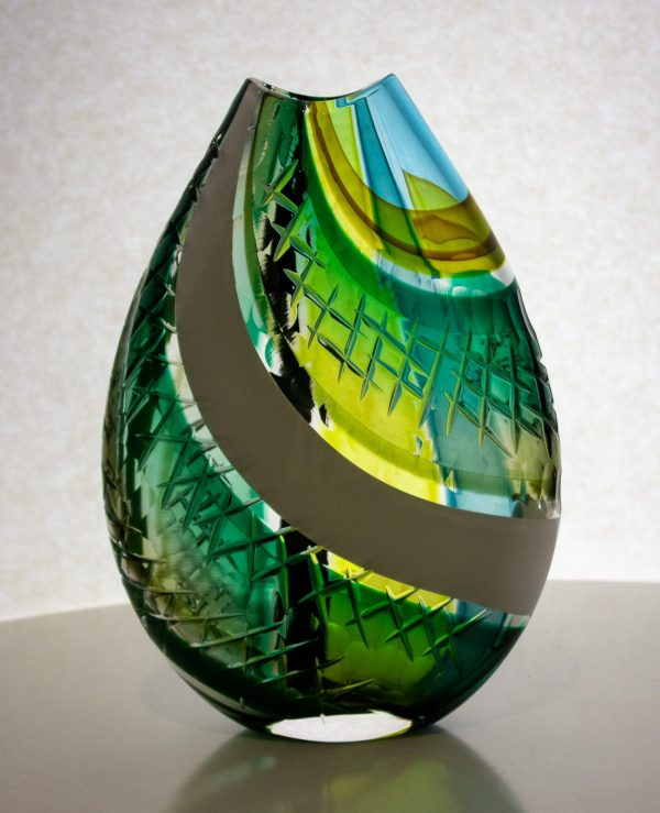 "Traditional art glass techniques combine with modern color and carving to create the perfect balance in this green, white and black flat vase. My origami pieces are so named because the first step in sculpting the rectangular mosaic is to fold it into a triangle. This results in the colored stripes on one side having a vertical orientation and the other side having a horizontal orientation. The handcarved and polished lens pattern corresponds to that movement. H - 10"" W - 7"" D - 2"""