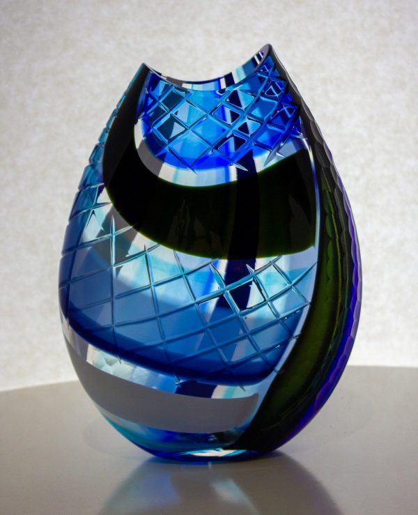 This blue and black vase with carving is truly incredible. The X cut carving mirrors the natural swooping curves of the colored stripes. My origami pieces are so named because the first step in sculpting the rectangular mosaic is to fold it into a triangle. This results in the colored stripes on one side having a vertical orientation and the other side having a horizontal orientation. The handcarved and polished lens pattern corresponds to that movement.