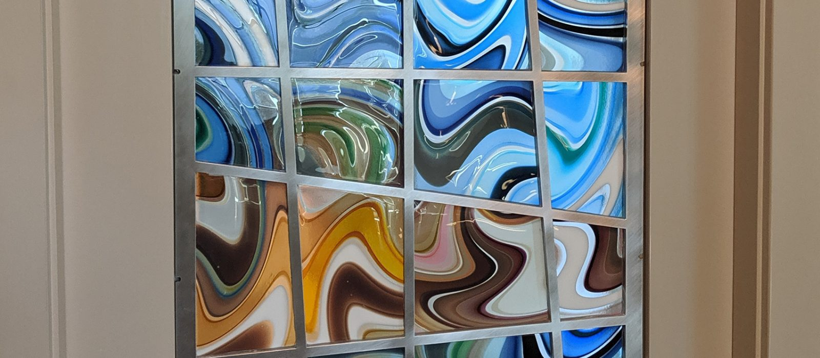 Amazing pocket door, made with striped blown glass panels set in metal