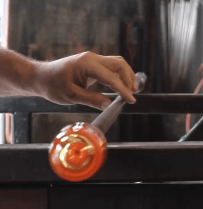 A hand turning a metal pipe with molten glass on the end.