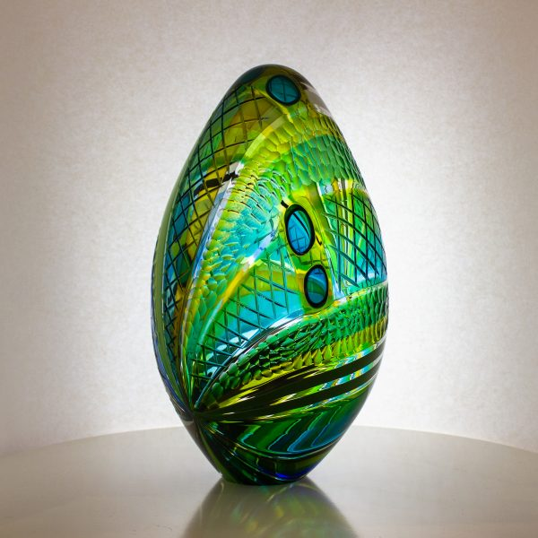 Large hand blown glass egg in stripes of green with carving on the outside.