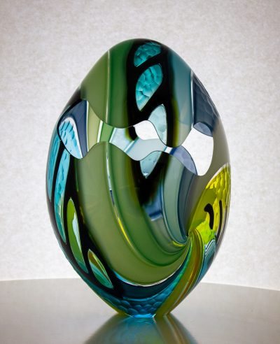 Fantastic green and blue striped egg with cut outs and texture carved on the outside.