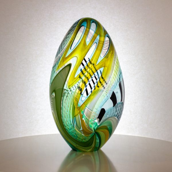 Hand blown glass egg in shades of green with oval shapes cut outs.