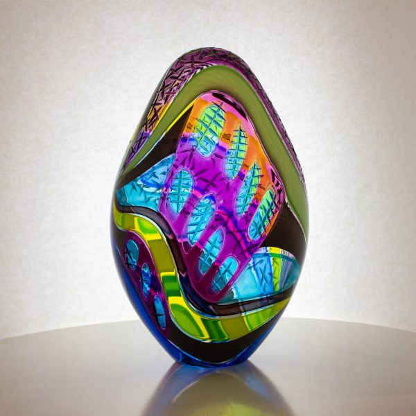 Incredible hand blown glass egg in a multitude of colors with carving on the surface.