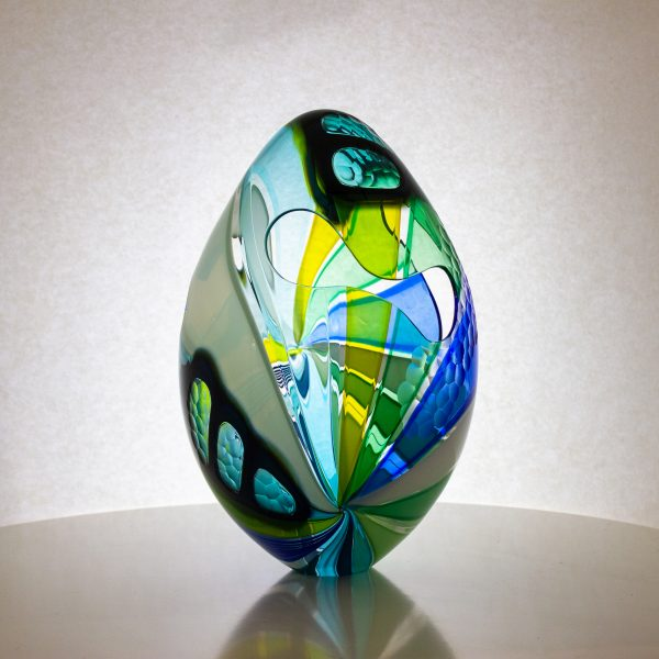 Green and blue striped hand blown glass egg. This egg has cut outs and carved texture on the surface.