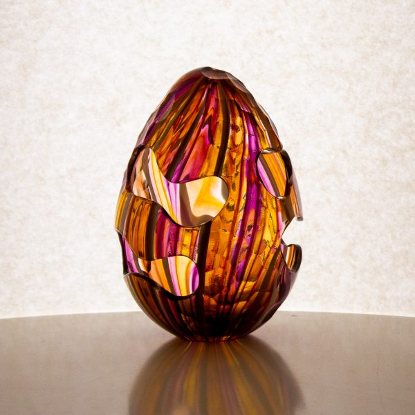 Small hand blown glass egg in orange and purples. This egg has cut outs and carving designed to distort the color pattern.