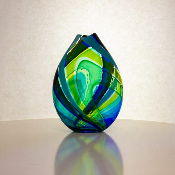 Beautiful blue and green hand blown flat vase with carving on the surface.